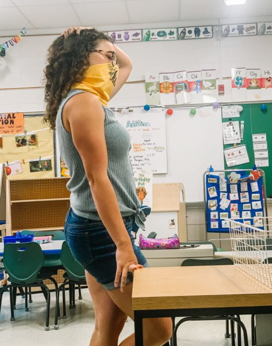teacher with face mask in an empty classroom